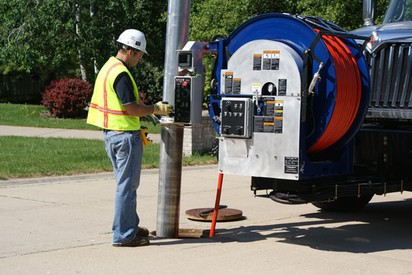 A Clean-Co employee cleans a storm drain with a jet rodder.